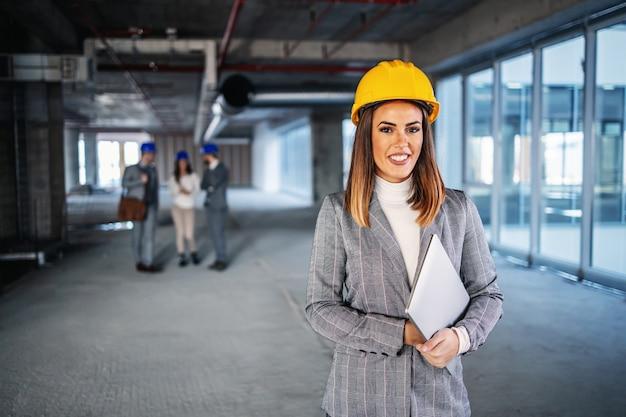 건설 과정에서 건물과 손에 노트북을 들고 내부 머리 서에 헬멧 젊은 성공적인 매력적인 백인 여성 건축가.