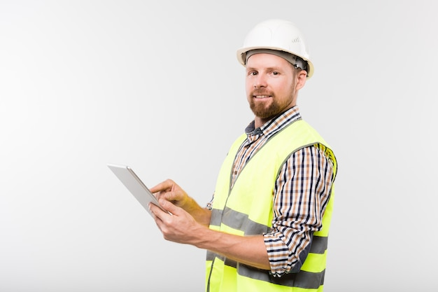 Young successful bearded builder in white hardhat, checkered shirt and yellow vest using tablet in front of camera