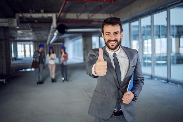Молодой успешный бородатый кавказский архитектор в костюме, стоящем внутри здания в процессе строительства и показывая большие пальцы руки вверх.
