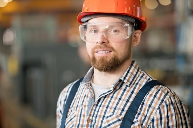 作業服、保護眼鏡、ヘルメットをかぶった若い成功したひげを生やした工場エンジニア
