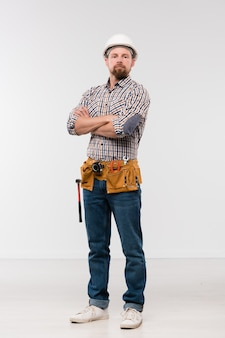 Young successful bearded repairman in white hardhat, checkered shirt and blue jeans standing in front of camera in isolation