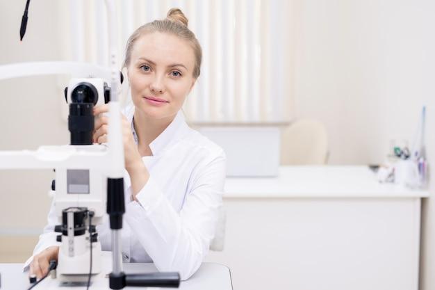 クリニックで働いている間に新しい眼科機器をテストしている若い成功した金髪検眼医