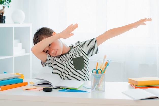 어린 성공한 소년은 내가 숙제를 끝냈을 때 손을 들고, 의기양양한 감탄사를 터뜨리고, 문제를 해결하고, 승리하고, 끝내고, 배움의 기쁨은 십대들을 motion dab trend 제스처로 만듭니다