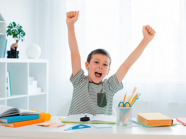 성공적인 어린 소년은 내가 숙제를 끝냈을 때 손을 들고, 의기양양한 느낌을 내고, 문제를 해결하고, 승리하고, 끝내고, 배움의 기쁨