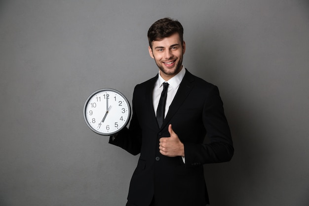 Young successful business man holding clock while showing thumb up gesture and