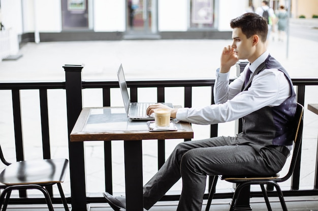 Young successful business man sitting in outdoor urban cafe with laptop and talking on phone