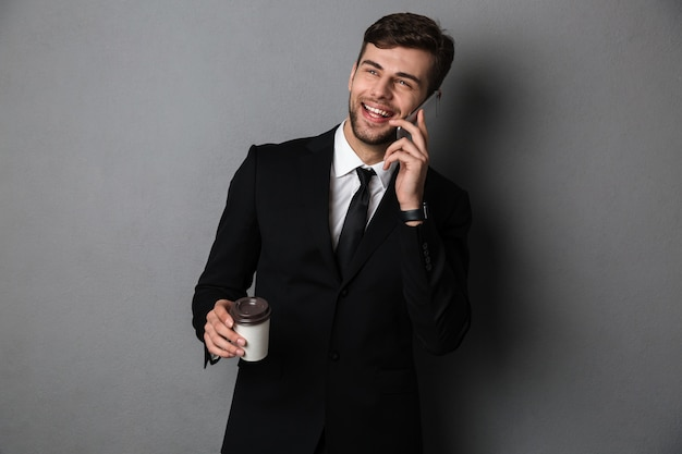 Young successful business man talking on mobile phone while holding cup of coffee, looking aside