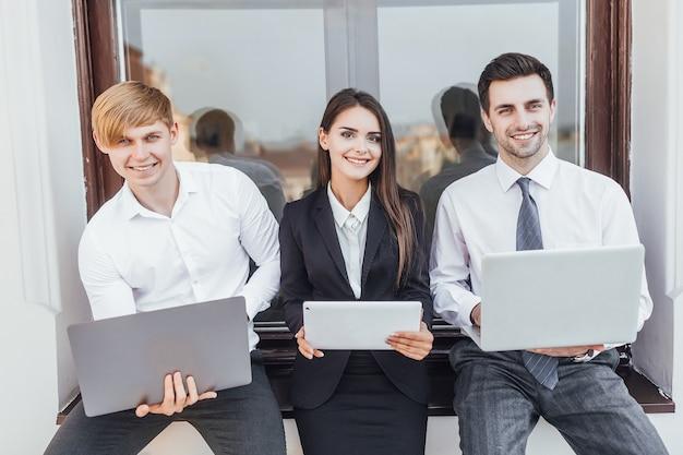 Молодые успешные деловые люди с ноутбуками в руках на улице