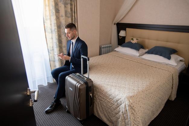 Молодой успешный деловой путешественник в костюме сидит на кровати и прокручивает в смартфоне, собираясь вызвать такси