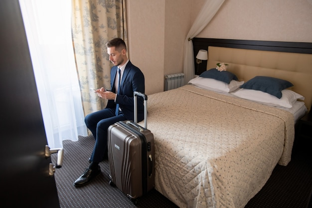 Young successful business traveler in suit sitting on bed and scrolling in smartphone while going to call taxi
