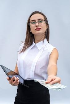 달러 지폐를 들고 태블릿 격리된 회색 배경을 사용하는 젊은 성공적인 비즈니스 여성.