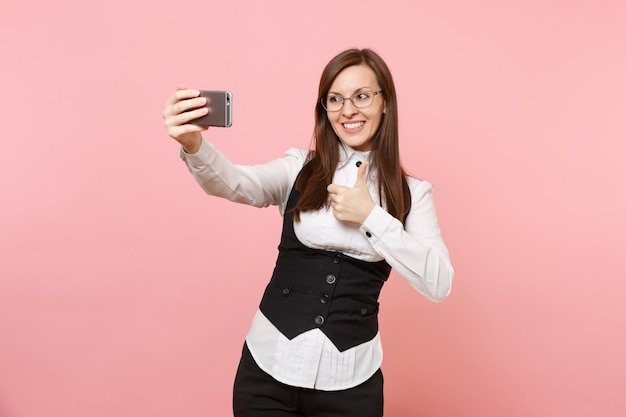 분홍색 배경에 격리된 엄지손가락을 보여주는 휴대폰으로 셀카를 찍고 있는 안경을 쓴 젊은 성공적인 비즈니스 여성. 여사장님. 성취 경력 부입니다. 광고 공간을 복사합니다.