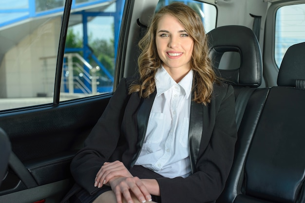 The young successful business woman traveling in the car.