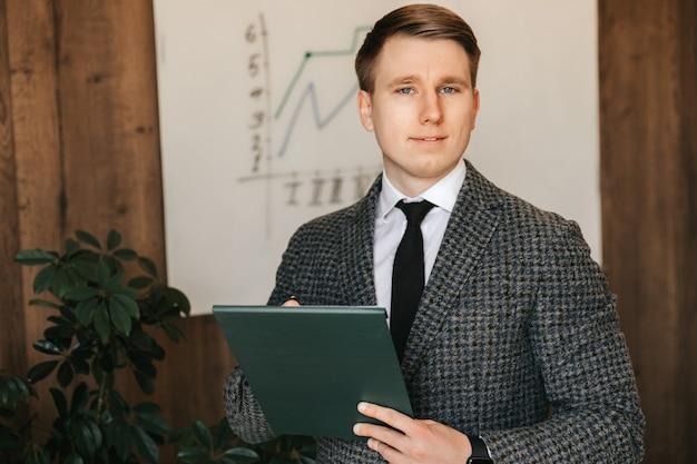Молодой успешный бизнесмен и офисный работник держит в руках папку с документами, делает заметки на бумаге