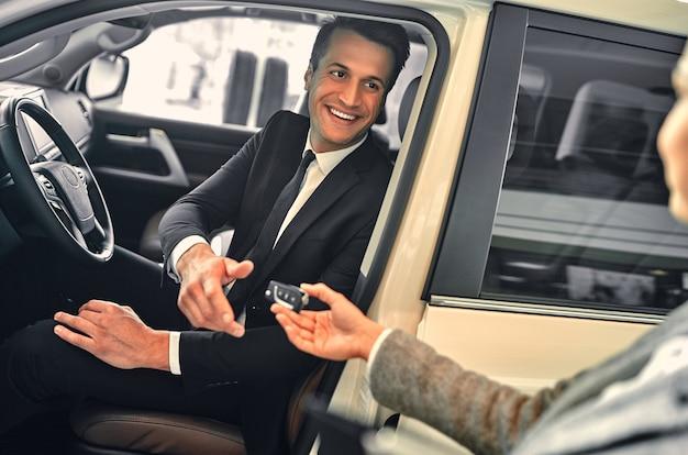 젊은 성공적인 사업가 새 차를 구입합니다. 판매자는 구매자에게 키를 제공합니다.
