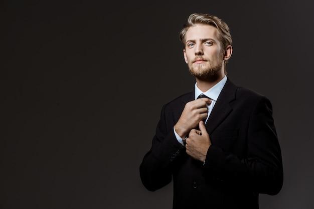 Молодой успешный бизнесмен, исправляя галстук