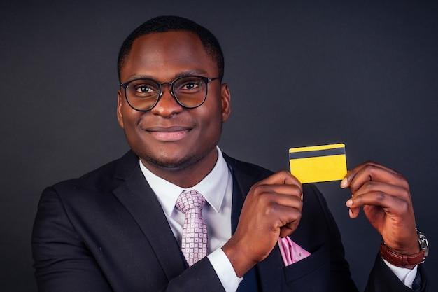 Молодой успешный бизнесмен кредитный брокер в стильном черном классическом костюме и в прохладных очках, держа желтую пластиковую кредитную карту в студии на темном фоне. концепция покупок