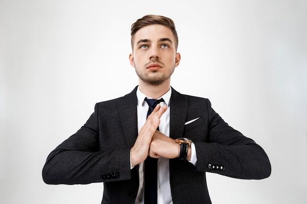 Молодой успешный бизнесмен в костюме позирует.