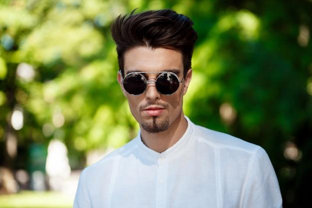 맑은 도시 주위를 산책하는 선글라스에 젊은 성공적인 사업가