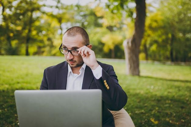 白いシャツ、古典的なスーツで若い成功した実業家は、手の眼鏡を修正します。男は柔らかいプーフに座って、屋外の緑の芝生の都市公園でラップトップpcコンピューターで作業します。モバイルオフィス、ビジネスコンセプト。