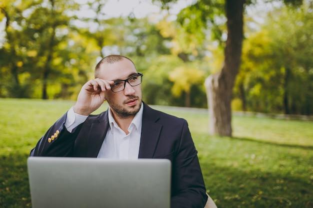 흰 셔츠, 고전적인 양복을 입은 젊은 성공적인 사업가는 손 안경을 수정합니다. 남자는 부드러운 푸프에 앉아 야외 녹색 잔디밭에 있는 도시 공원에 있는 노트북 컴퓨터에서 일합니다. 모바일 오피스, 비즈니스 개념입니다.