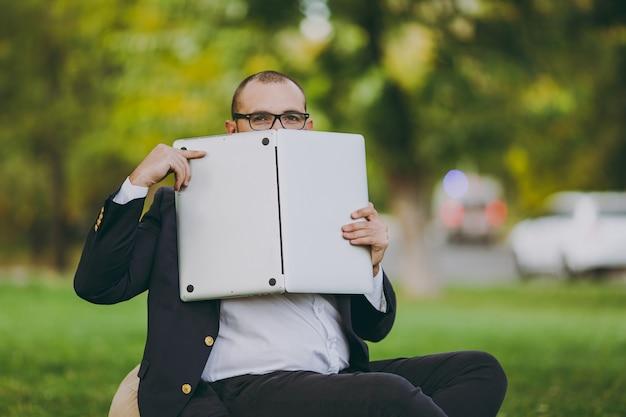 흰 셔츠, 고전적인 양복, 안경을 쓴 성공적인 젊은 사업가. 남자는 부드러운 푸프에 앉아 도시 공원의 노트북 컴퓨터 뒤에 숨어 자연의 야외 잔디밭에 있습니다. 모바일 오피스, 비즈니스 개념입니다.