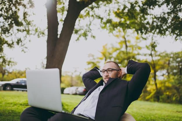흰 셔츠, 고전적인 양복, 안경을 쓴 성공적인 젊은 사업가. 남자는 부드러운 푸프에 앉아 머리 뒤로 손을 잡고 야외 녹색 잔디밭에 있는 도시 공원의 노트북 컴퓨터에서 일합니다. 모바일 오피스 개념입니다.