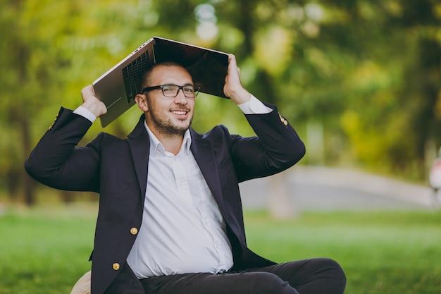 白いシャツ、古典的なスーツ、眼鏡で若い成功した実業家。男は、自然の屋外の緑の芝生の都市公園でカバーラップトップpcコンピューターの下の柔らかいプーフに座っています。モバイルオフィス、ビジネスコンセプト。