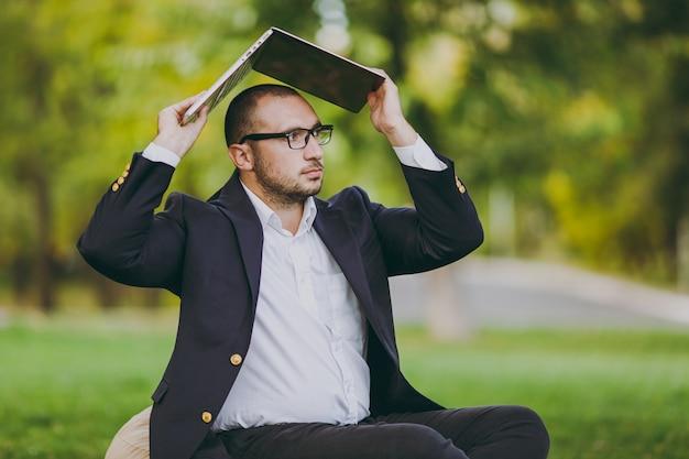 흰 셔츠, 고전적인 양복, 안경을 쓴 성공적인 젊은 사업가. 남자는 자연의 야외 녹색 잔디밭에 있는 도시 공원에 있는 덮개 노트북 pc 아래 부드러운 푸프에 앉아 있습니다. 모바일 오피스, 비즈니스 개념입니다.