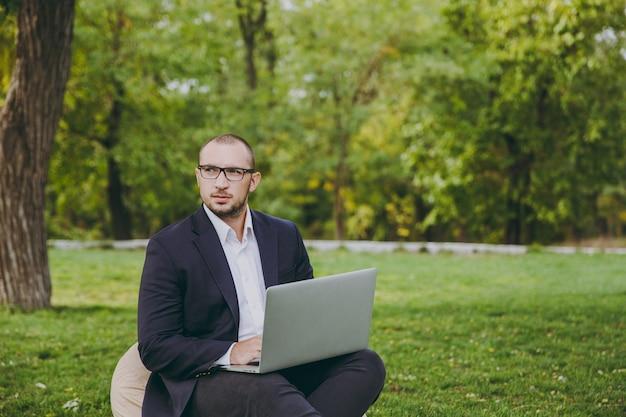 Молодой успешный бизнесмен в белой рубашке, классическом костюме, очках. человек сидит на мягком пуфе, работая на портативном компьютере в городском парке на зеленой лужайке на открытом воздухе на природе. мобильный офис, бизнес-концепция.