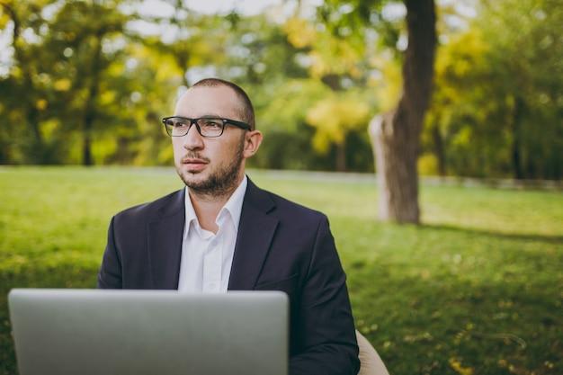 白いシャツ、古典的なスーツ、眼鏡で若い成功した実業家。男は柔らかいプーフに座って、自然の屋外の緑の芝生の都市公園でラップトップpcコンピューターに取り組んでいます。モバイルオフィス、ビジネスコンセプト。
