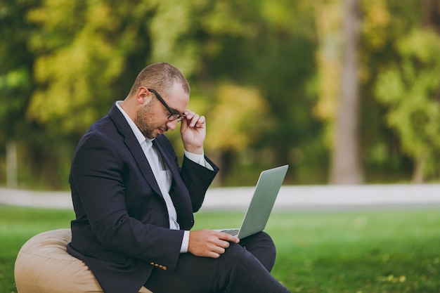 흰 셔츠, 고전적인 양복, 안경을 쓴 성공적인 젊은 사업가. 남자는 자연의 야외 녹색 잔디에 도시 공원에서 노트북 pc 컴퓨터에서 작업, 부드러운 pouf에 앉아. 모바일 오피스, 비즈니스 개념입니다.