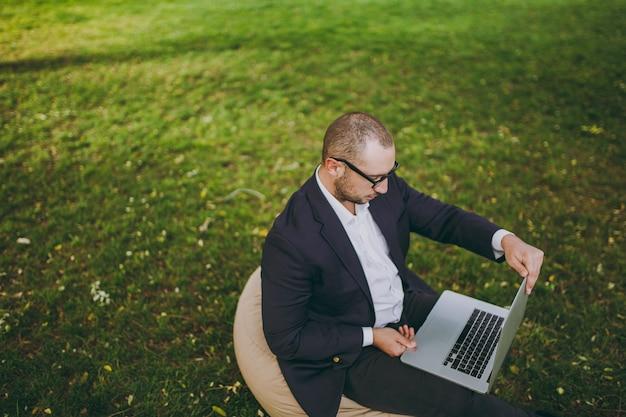 흰 셔츠, 고전적인 양복, 안경을 쓴 성공적인 젊은 사업가. 남자는 자연의 야외 녹색 잔디에 도시 공원에서 노트북 pc 컴퓨터에서 작업, 부드러운 pouf에 앉아. 모바일 오피스 개념입니다. 평면도.