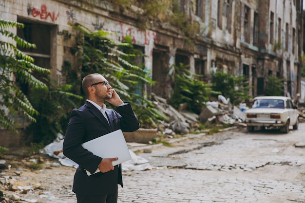 흰 셔츠, 고전적인 양복, 안경을 쓴 성공적인 젊은 사업가. 노트북 pc를 들고 서 있는 남자, 폐허, 파편, 야외 석조 건물 근처에서 전화 통화를 하고 있습니다. 모바일 오피스, 비즈니스 개념입니다.