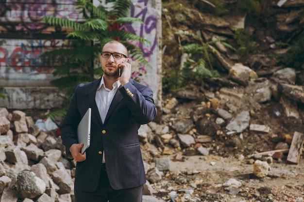 Молодой успешный бизнесмен в белой рубашке, классическом костюме, очках. человек, стоящий с портативным компьютером, разговаривает по телефону возле руин, обломков, каменного здания на открытом воздухе. мобильный офис, бизнес-концепция.