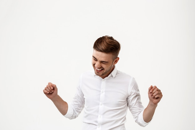 Young successful businessman laughing, rejoicing.