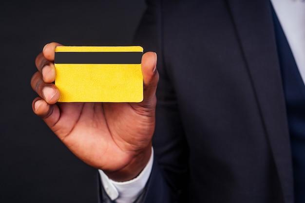 Молодой успешный бизнесмен человек в стильном черном классическом костюме и в прохладных очках, держа желтую пластиковую кредитную карту в студии на темном фоне. концепция покупок