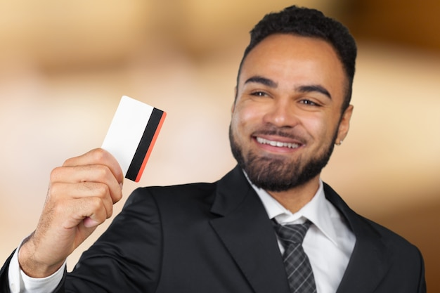 Young successful businessman man in a stylish black classic suit holding a plastic credit card