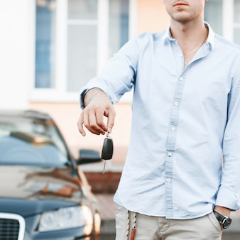 Young successful businessman offering a car key