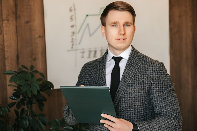 Young successful businessman and office worker holds a folder with documents in his hands makes notes on paper