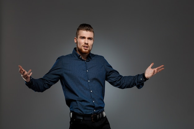 Young successful businessman posing over dark wall.