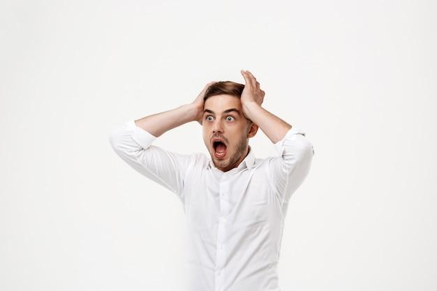 Young successful businessman shouting, panic.