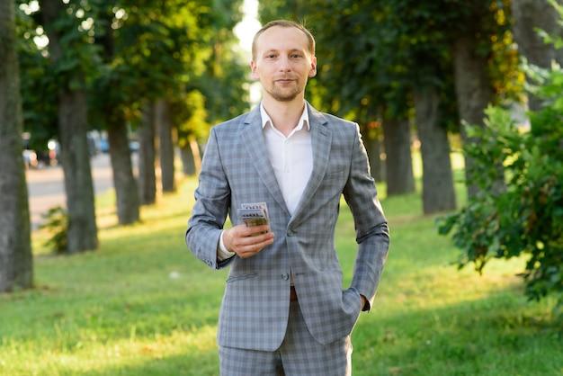 若い成功した実業家は彼の手でお金を示しています。