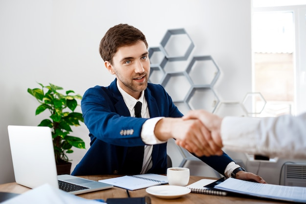 Молодой успешный бизнесмен сидя на рабочем месте, предпосылка офиса.
