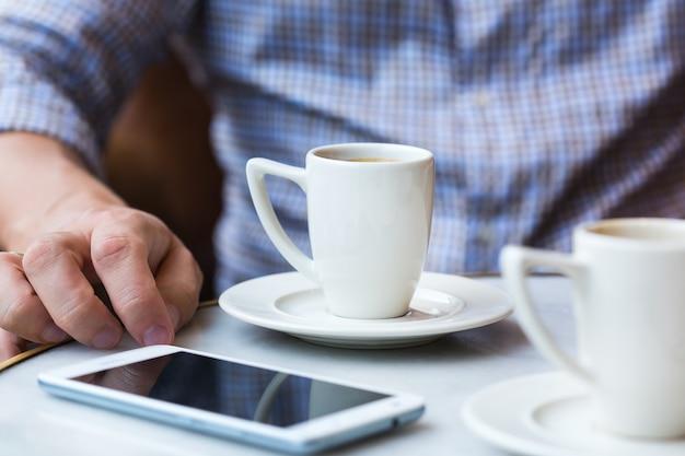 カフェに座って、朝のコーヒーを飲み、スマートフォンを使用して成功した若い実業家。自然光のあるライフスタイル構成