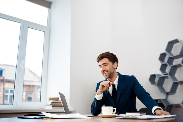 Young successful businessman sitting at workplace, office background.