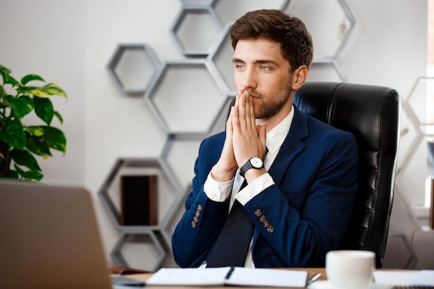 Giovane riuscito uomo d'affari che si siede nel luogo di lavoro, fondo dell'ufficio.