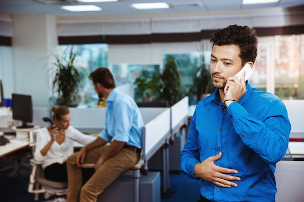 Young successful businessman speaking on phone, smiling, over office