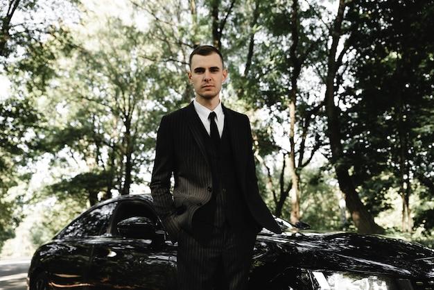 若い成功した実業家は彼の高価な車の前に立っています。金持ちの若い男。金持ち。ビジネスマンの背景に車。結婚式の日に車で新郎