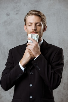 Young successful businessman in suit holding money